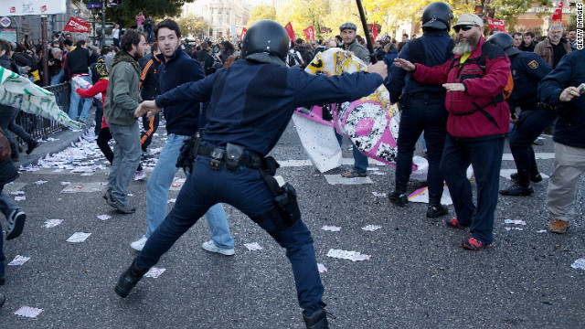 A riot policeman swings his baton at protesters during a demonstration at Cibeles Square on November 14, 2012 in Madrid, Spain. A coordinated general strike by unions in Spain and Portugal has paralysed public transport in the two countries with further strikes planned across Europe