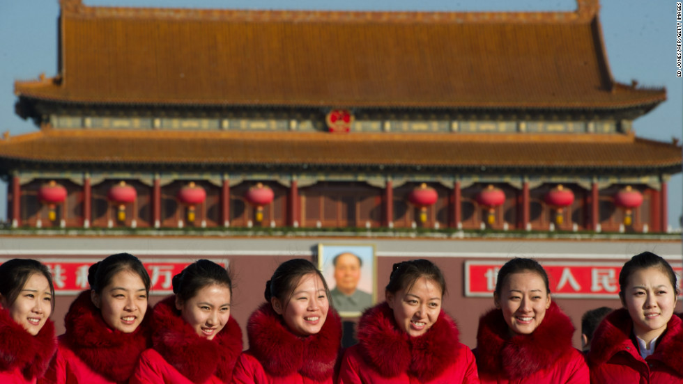 Hostesses pose before the gate to Tiananmen Square as delegates arrive at the Great Hall of the People for the start of the closing ceremony of the Communist Party Congress on November 14.  The week-long congress will end with a transition of power within the party, most notably, introducing new members of the Politburo Standing Committee, which effectively runs China.