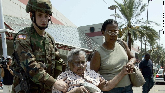 A National Guard member pushes an elderly victim of Hurricane Katrina in an office chair to a food and water distribution line.