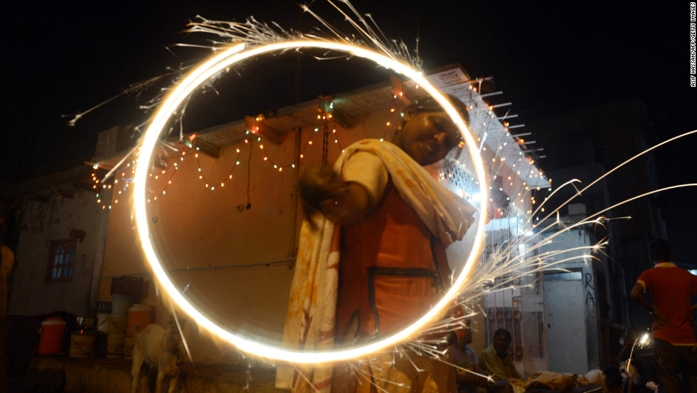 "A  reveler waves sparklers during Diwali, the festival of lights, in Karachi, Pakistan, on Tuesday. The word Diwali itself means ""festival of lamps"", because houses and public spaces are decorated with scores of small oil lamps in honor of the goddess Lakshmi, to whom Hindus pray to for success and wealth."