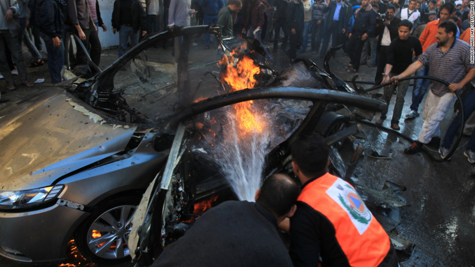 Palestinian firefighters extinguish fire from the car in which al-Jaabari was apparently riding.