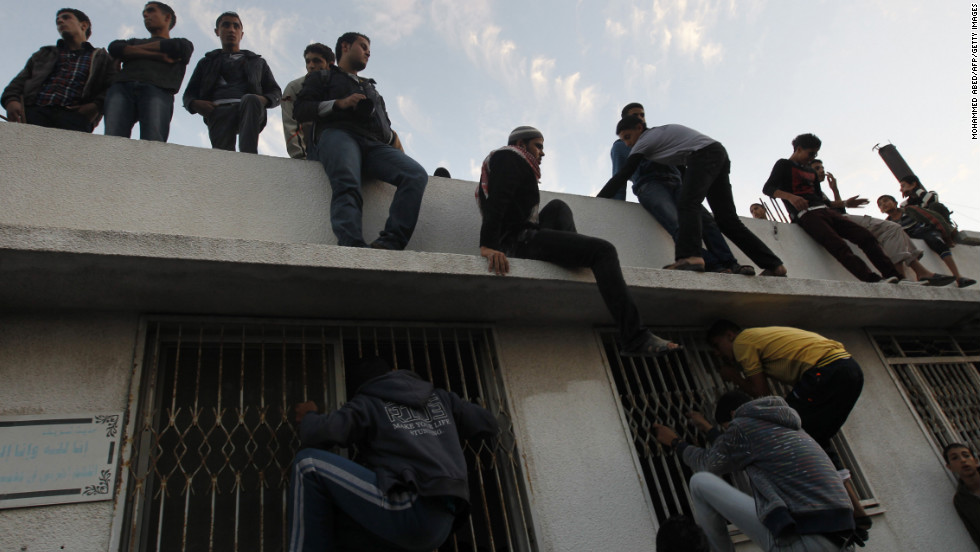Palestinian youths look inside a building where al-Jaabari's body was brought after the attack.