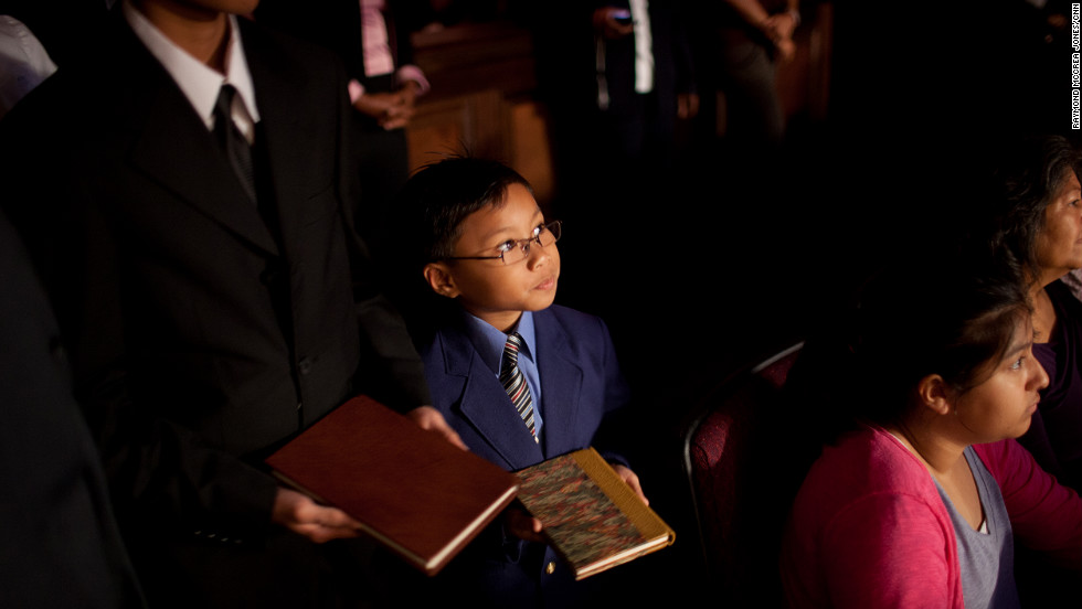 A child lines up with a group of children at First Baptist Church Atlanta, carrying a book written by Charles Stanley. Each child carried one book representing the 45 books written by Stanley during his career. They placed the book on a shelf in front of the sanctuary.