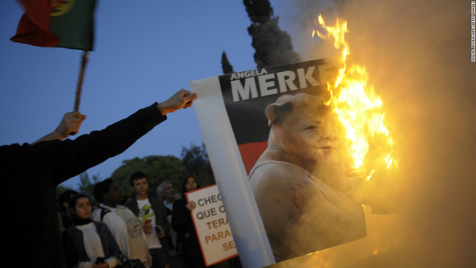 Protesters burn a picture of Angela Merkel in Belem, on the outskirts of Lisbon, on November 12, 2012.