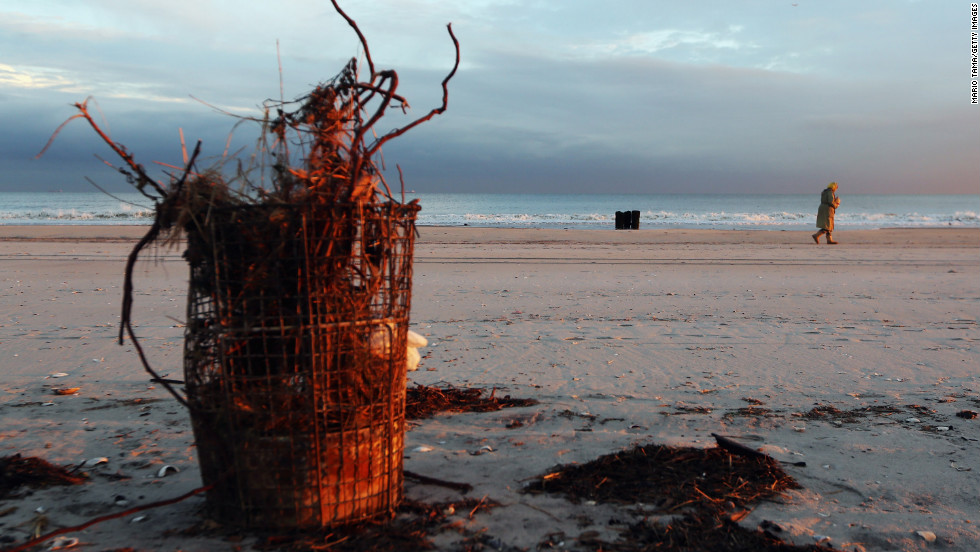 A woman walks past debris on Rockaway Beach on Tuesday.