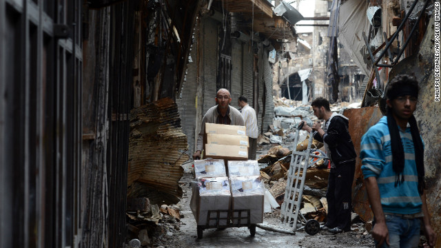 A Syrian man moves his belongings from his damaged shop in the old city of Aleppo on November 12, 2012