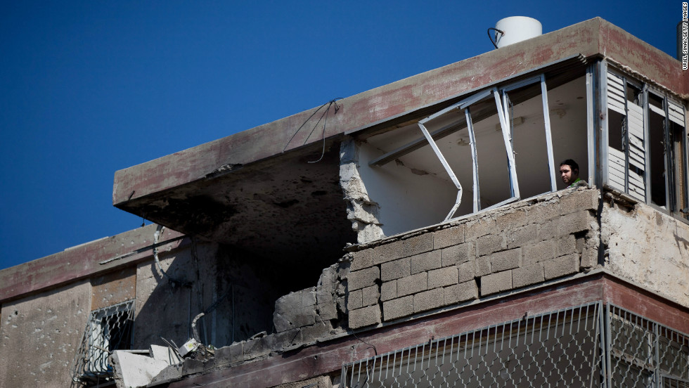An Israeli man looks out from an apartment building that was hit by a rocket launched presumably from the Gaza Strip, claiming three lives on Thursday, November 15, in Kiryat Malachi, Israel.