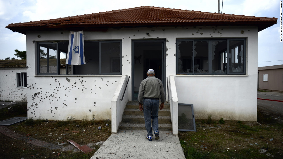 An Israeli man walks to his house damaged by a rocket fired by Palestinian militants from the Gaza Strip in the moshav of Sde Uziyahu near the southern Israeli city of Ashdod.  The Israeli military said it had sealed off all main roads around Gaza and declared a closed military zone, in the latest sign it was poised to launch a first ground offensive on the Palestinian enclave since December 2008-January 2009.