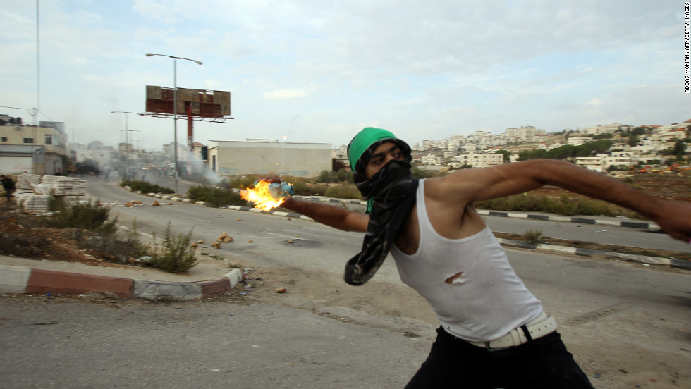 A student from the University of Birzeit throws a molotov cocktail toward Israeli soldiers during clashes.