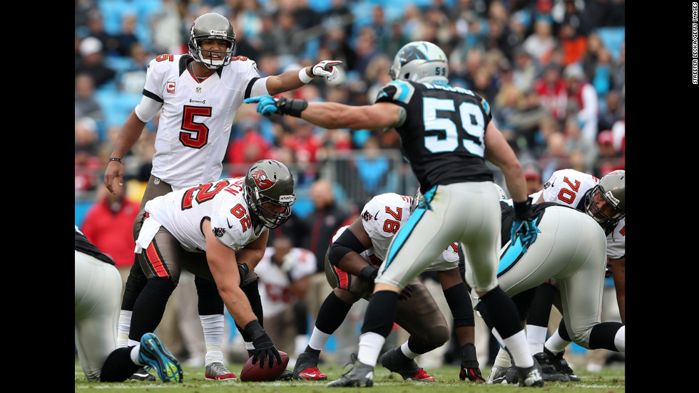 Josh Freeman of the Buccaneers points across the line as Luke Kuechly of the Panthers points on Sunday.