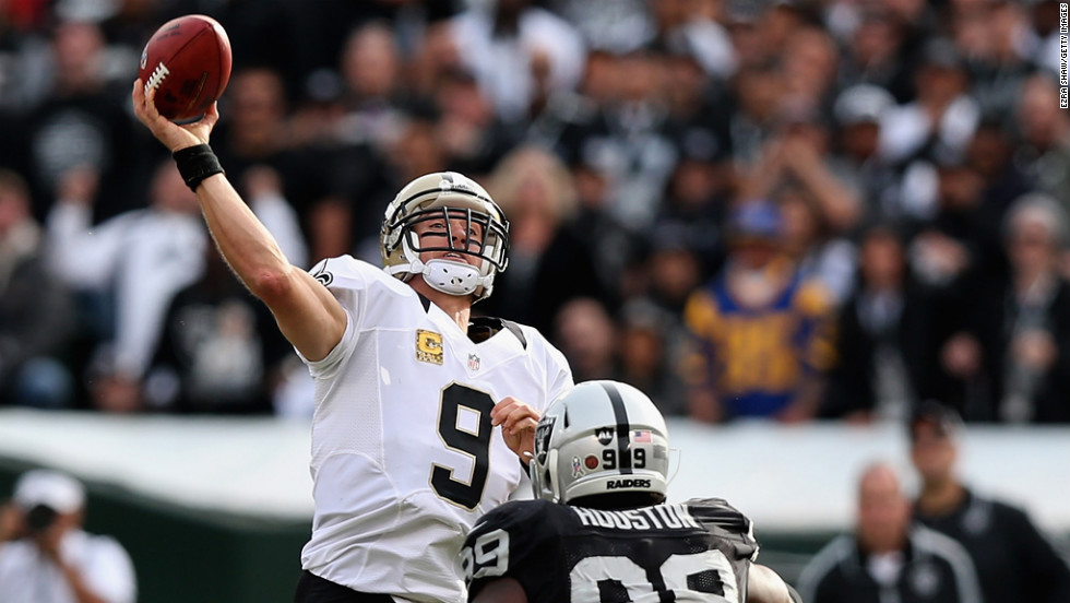Drew Brees of the New Orleans Saints throws a long touchdown pass to Lance Moore in the second quarter before being hit by Lamarr Houston of the Oakland Raiders at O.co Coliseum on Sunday in Oakland, California.