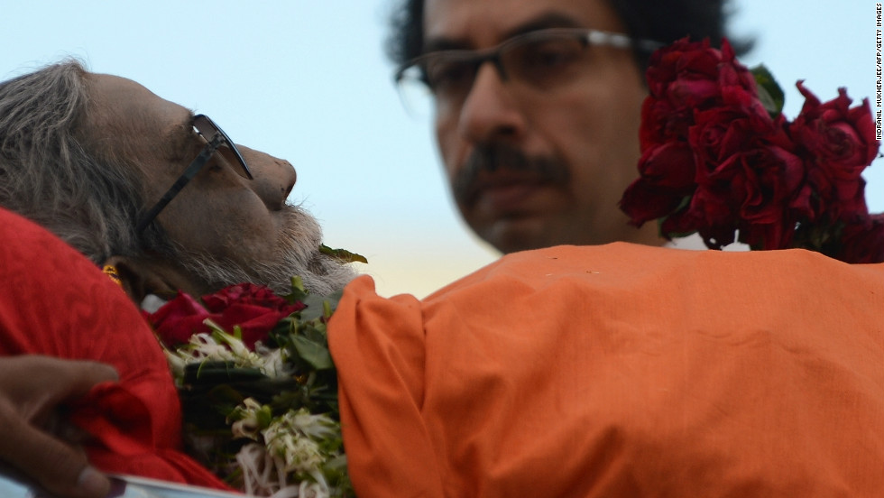The body of  Bal Thackeray is watched by his son Uddhav Thackeray (R) as it is carried through a sea of supporters during the funeral procession.