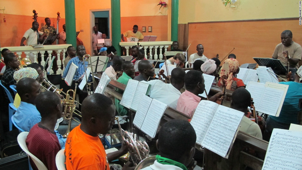 Conductor Armand Diangienda (far right) is the founder and conductor of the Orchestre Symphonique Kimbanguiste. Their rehearsal room, in his house, can barely fit the ensemble of some 200 people.