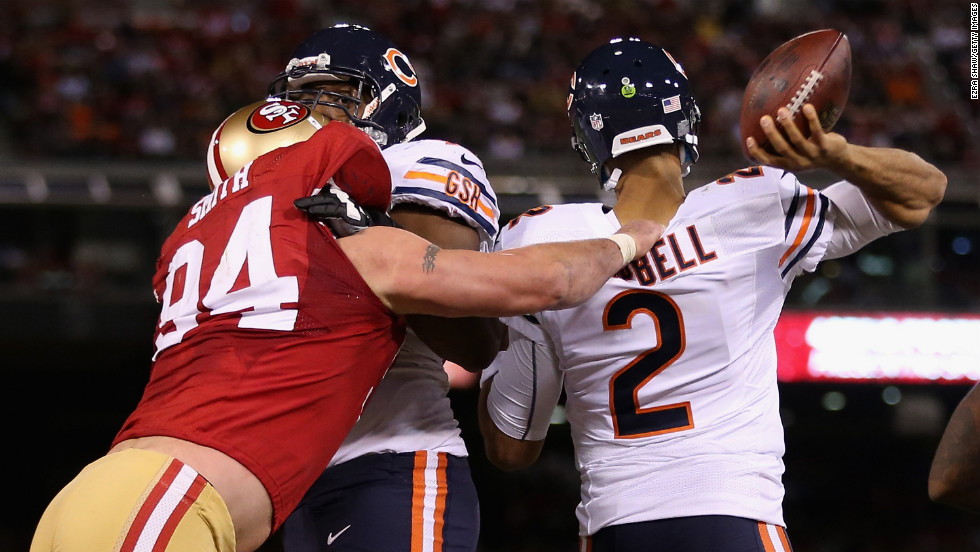 Justin Smith of the 49ers grabs the jersey of Bears quarterback Jason Campbell as he tries to pass the ball Monday.