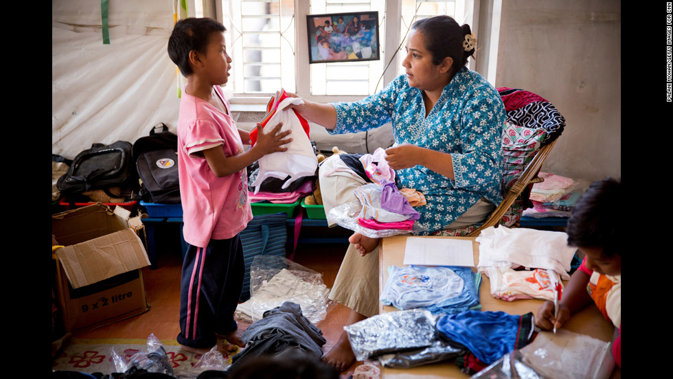 "Basnet hands out new clothes to one of the young children she cares for in Kathmandu. The children reciprocate her love by calling her ""Mamu,"" which means ""mommy."""