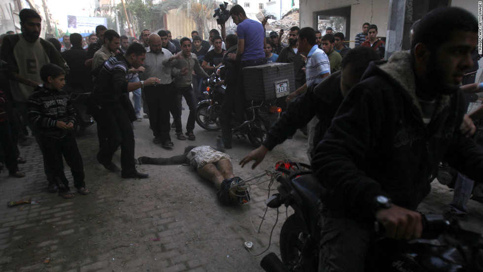 <strong>November 20:</strong> Men on motorcycles drag the body of a man through the streets of Gaza City. The men dragging the body claimed it was the body of a collaborator and an Israeli spy. Hamas and Israel agreed to a cease-fire on November 21 after eight days of round-the-clock warfare.