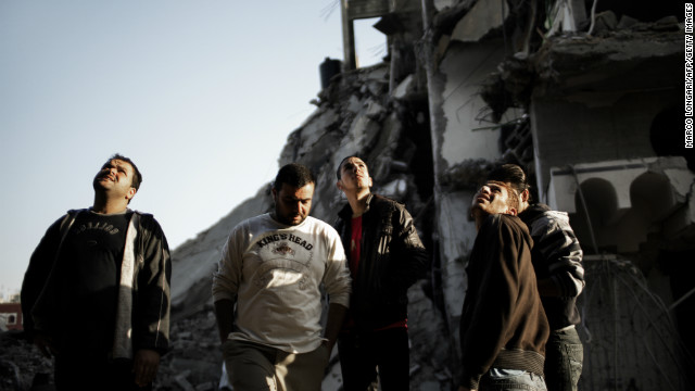 Palestinians stare at a house destroyed by an Israeli airstrike on Gaza City on November 20, 2012.