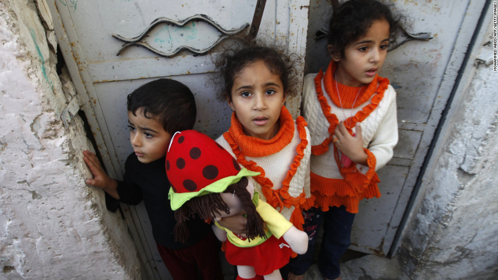 Palestinian children stand at the gate of their home Tuesday as they watch a funeral procession for those killed following an Israeli airstrike in northern Gaza.
