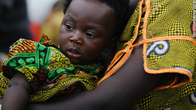 A displaced Congolese woman and her child sit inside a United Nations base in Monigi, 5km from Goma