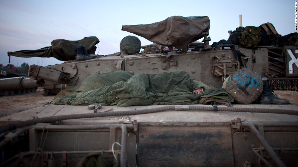 An Israeli soldier sleeps in a deployment area Wednesday on Israel's border with Gaza.
