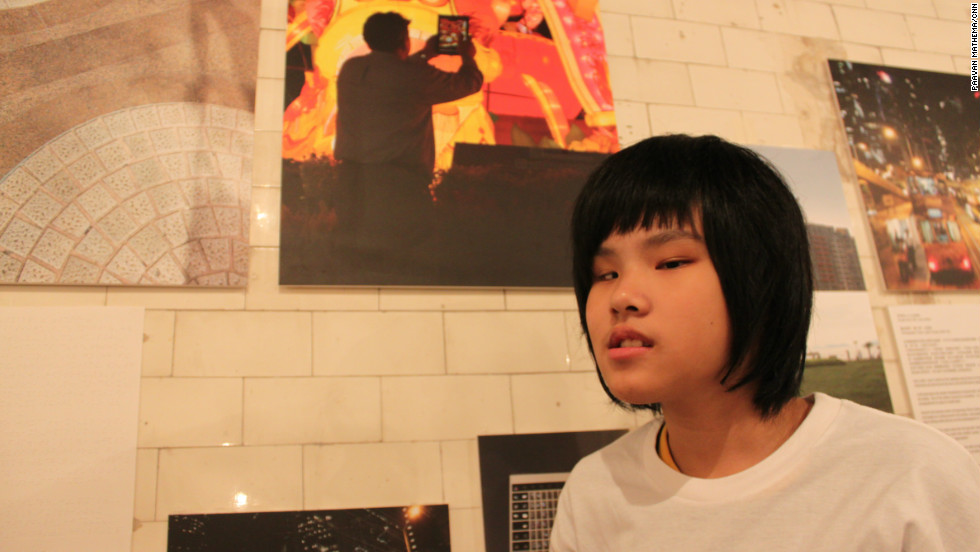 Yuen Wing Sz, who has partial vision, stands with a picture she took during the Mid- Autumn festival in Hong Kong.