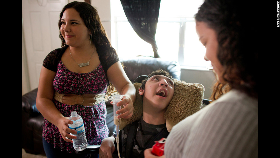 Mimi feeds Isaac while their mother, Rose Santiago, looks on. Often, Siskowski says, young caregivers find themselves overburdened by the extra responsibility and fall behind in school. They can also feel depressed, anxious and isolated.