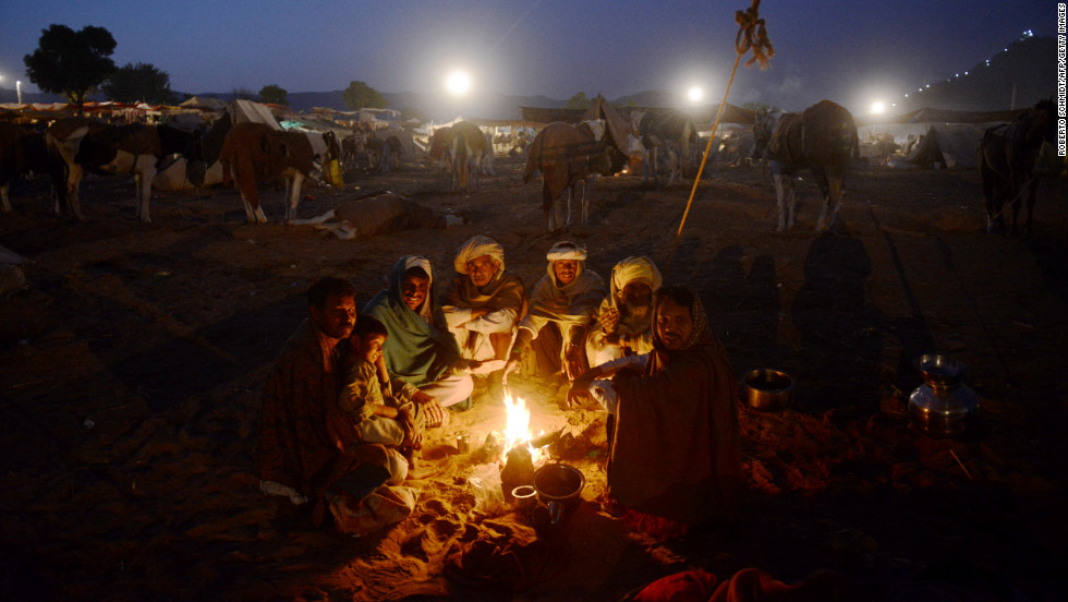A group of camel traders sit around a fire in the early morning hours on Wednesday.