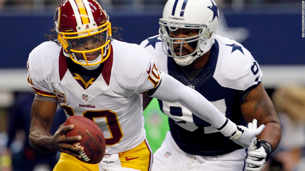 Redskins quarterback Robert Griffin III scrambles with the ball before being sacked by Jason Hatcher of the Cowboys.