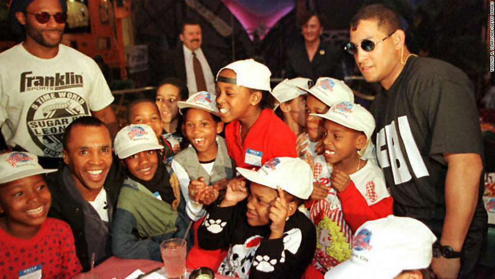 Boxers Sugar Ray Leonard, sitting second from left, and Hector Camacho, right, pose with kids from a New Jersey school during a benefit luncheon at Planet Hollywood in Atlantic City on February 28, 1997.