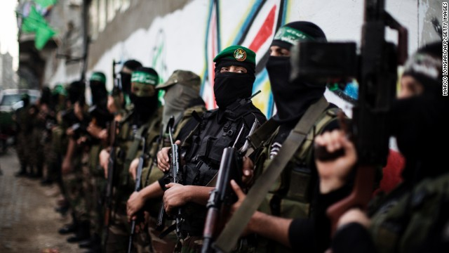 Hamas gunmen line up outside the house of their late leader Ahmed Jaabari in Gaza City on Thursday.
