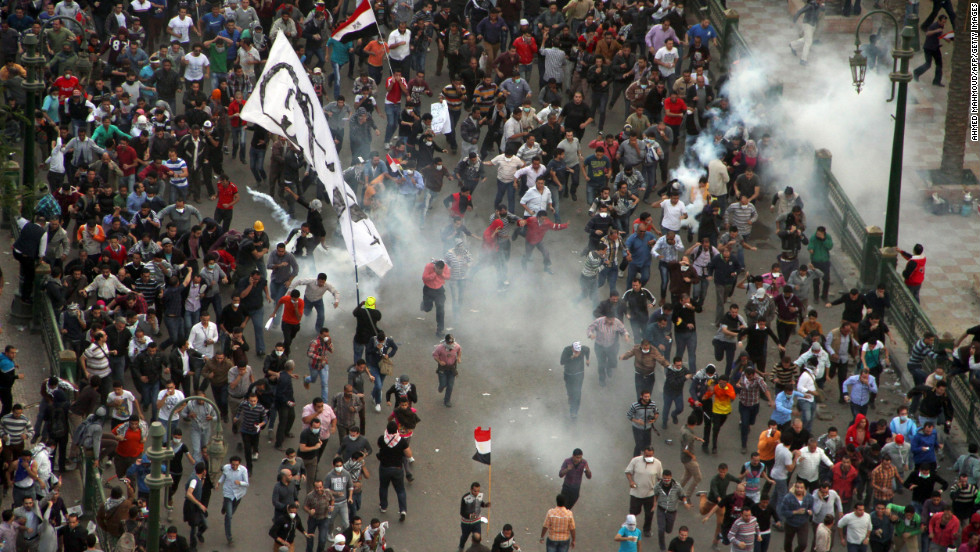 Protesters demonstrating against Morsy run from tear gas fired by Egyptian riot police during clashes in Cairo's Tahrir Square on Friday.