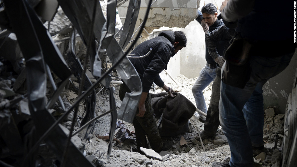 Rescue workers cover a corpse under the debris outside Dar Al-Shifa hospital in Aleppo on Thursday.