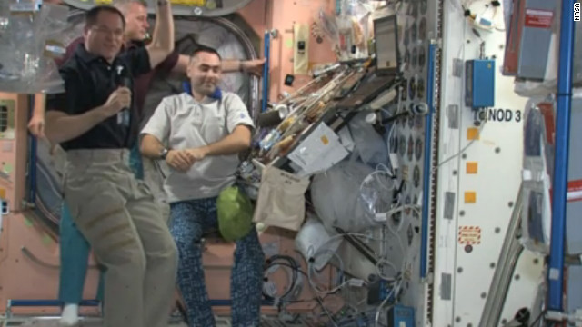 Space station crew members, from left, Kevin Ford, Oleg Novitskiy and Evgeny Tarelkin preview their Thanksgiving spread.
