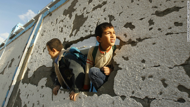 Palestinian schoolboys look through a hole at their damaged school in Gaza City on Saturday, November 24.