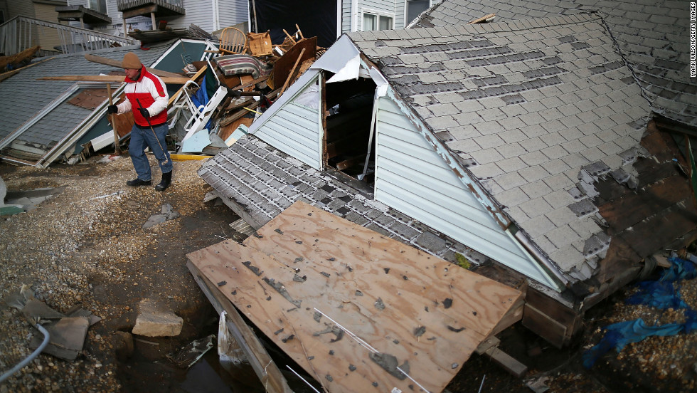 "David McCue stands near the roof of his beach house, which was completely demolished by Superstorm Sandy, in Ortley Beach, New Jersey, on Sunday, November 25. <a href=""http://www.cnn.com/2012/10/30/us/gallery/sandy-damage/index.html"" target=""_blank""><strong>See photos of the immediate aftermath of Sandy.</a></strong>"