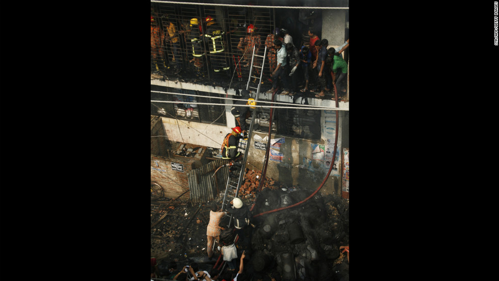 Firefighters climb a ladder November 26. Reports suggested that the fire started on the ground floor and the building had no emergency exits.