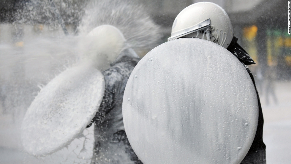 """A police officer uses a shield to protect himself from milk sprayed by dairy farmers during a protest against European Union agricultural policies in Brussels, Belgium, on Monday, November 26. During the """"1,000 tractors to Brussels"""" demonstration, farmers rolled up to the European Parliament with tractors and fake cows to call for political leaders to act on falling milk prices caused by overproduction in Europe."""