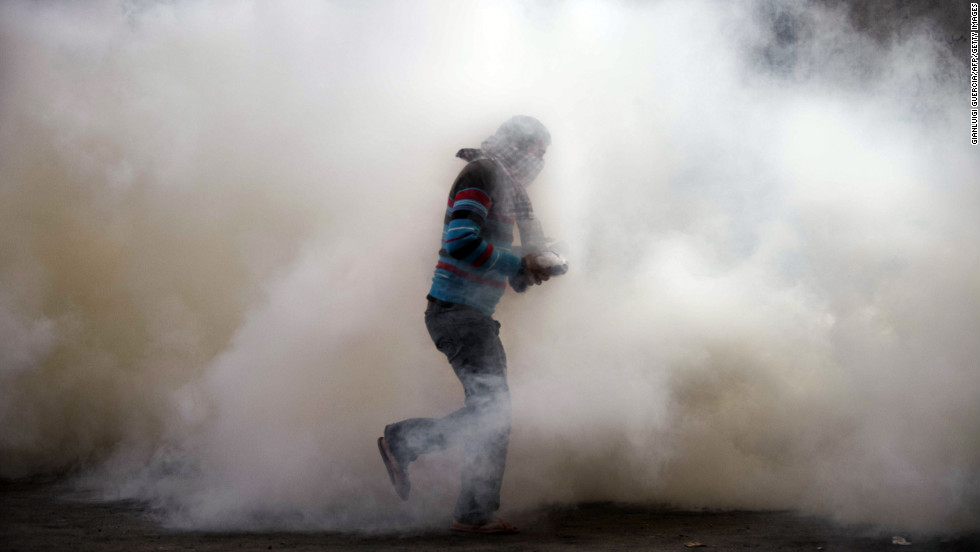 An Egyptian protester attempts to throw back a tear gas canister on Tuesday during clashes with riot police in Omar Makram Street, off Tahrir Square.