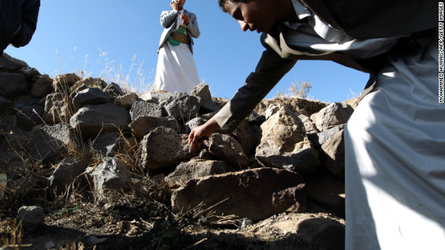 Yemeni men inspect the site where a Saudi diplomat and his bodyguard were killed, in Sanaa on November 28.