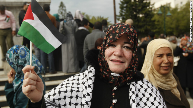A Palestinian woman hold up a small Palestinian flag as she takes part in a rally in support of the efforts of Palestinian President Mahmud Abbas to secure a diplomatic upgrade at the United Nations in Gaza City on November 27, 2012.