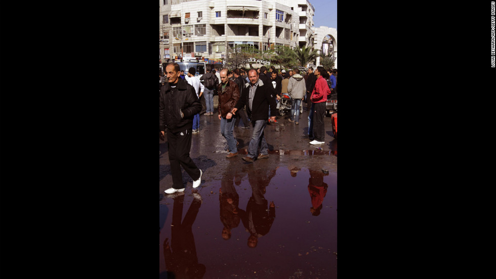 Syrian men walk around a pool of blood at the site of a car bomb explosion in Jaramana on Wednesday.