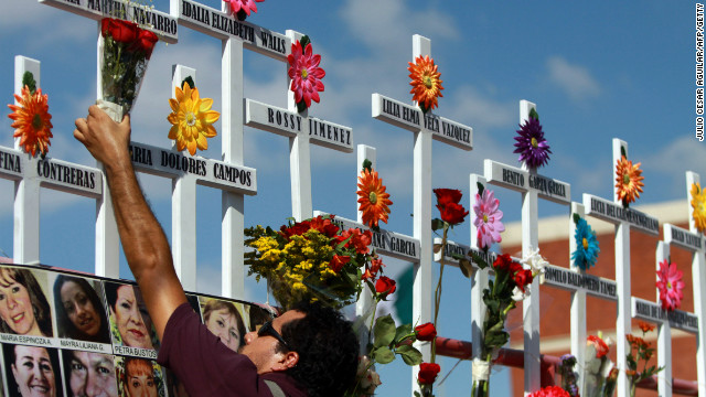 A relative of victims of the Casino Royale puts flowers on a cross during the commemoration of the first anniversary of the crime in Monterrey, Mexico, on August 25, 2012. 52 people died on August 25, 2011, when members of Los Zetas drug cartel doused the Casino Royale with gasoline and set it ablaze.