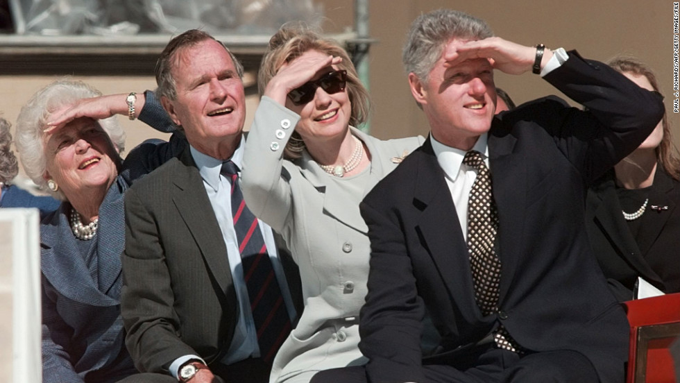 President Bill Clinton and former President George H.W. Bush watch the U.S. Army's Golden Knights parachute team during the dedication ceremony for Bush's presidential library at Texas A&M University in College Station Texas in November 1997.