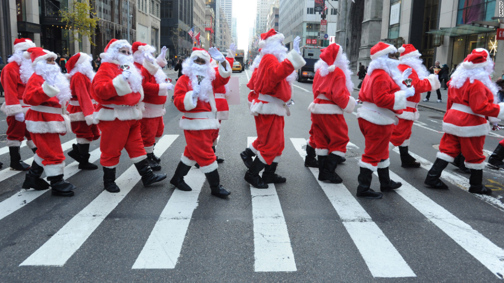 Volunteers in New York's 110th annual Sidewalk Santa Parade cross the street on Friday, November 23.
