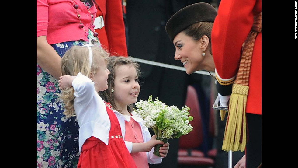 Catherine speaks with two young girls as she presents shamrocks to members of the 1st Battalion Irish Guards at the St Patrick's Day Parade on March 17, 2012, at Mons Barracks in Aldershot.