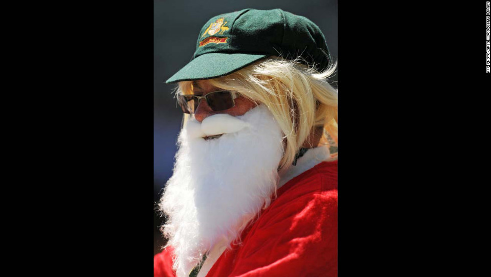 A spectator dressed as Santa Claus and wearing an Australian green cap watches the South African team walk out onto the field at a cricket match against Australia on December 3.