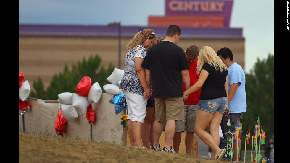 "<strong>July 28:</strong> Visitors gather and pray around a cross erected at a memorial set up across the street from the Century 16 movie theater in Aurora, Colorado. James Holmes is suspected of killing 12 people and injuring 58 others during a shooting rampage on July 20 at a screening of ""The Dark Knight Rises."""