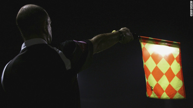 A file photo of a linesman raising his flag during a soccer match.
