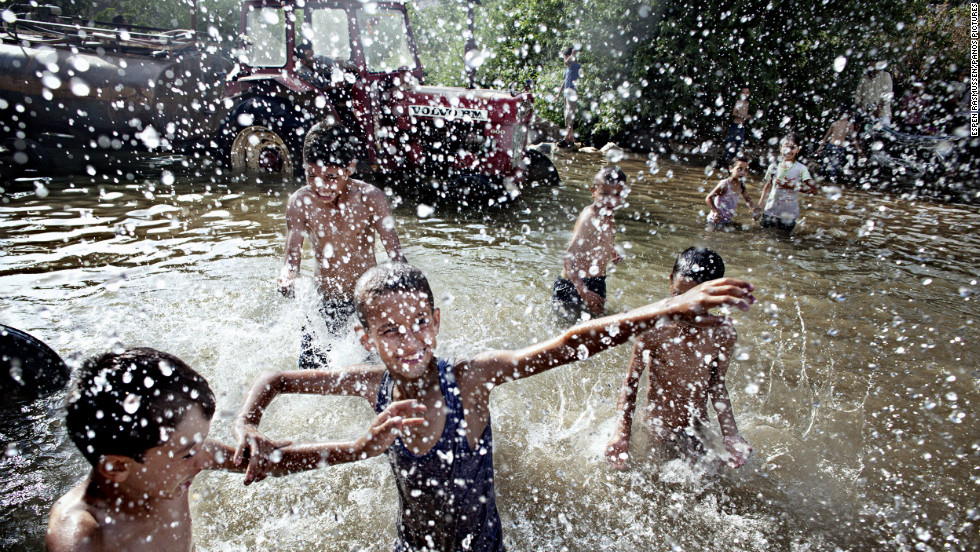 <strong>June 15:</strong> Lebanese children and Syrian refugees play in a natural spring close to the Syrian border. Behind them, a line of trucks and tractors collect fresh water to supply villages in the area. Tens of thousands of people have fled from Syria to Lebanon since the conflict started.