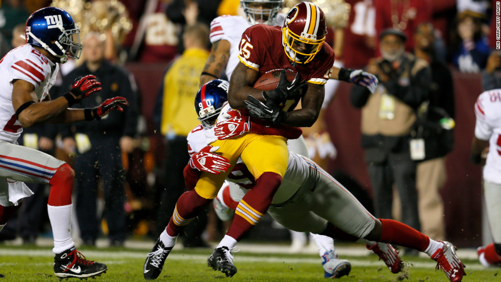 "Josh Morgan of the Washington Redskins runs the ball as he is hit by Jason Pierre-Paul of the New York Giants before scoring a touchdown after recovering a fumble on Monday, December 3, at FedExField in Landover, Maryland. Check out the action from Week 13 of the NFL, and <a href=""http://www.cnn.com/2012/11/22/football/gallery/nfl-week-12/index.html"">look back at the best photos from Week 12</a>."